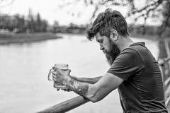 Concept de bière de métier L'homme barbu tient la tasse de bière, boit de la bière extérieure L'homme avec la longue barbe semble photographie stock libre de droits