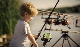 Concept de bonheur d'enfants d'enfance d'enfant Le petit garçon apprennent à pêcher des poissons en lac ou rivière Photo stock