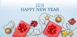 Concept de 2019 bonnes années, boîtes de cadeaux ou boîtes de présents avec les arcs, l'étoile et la boule rouges sur le fond ble photos libres de droits