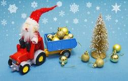 Concept de célébration de vacances de Noël Santa Claus portant des boules de Noël sur le tracteur avec la remorque Photo libre de droits