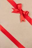 Concept de cadeau - arc et ruban rouges sur le carton images stock