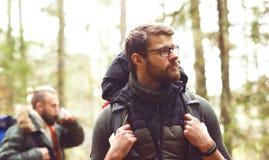 Concept de camp, d'aventure, de déplacement et d'amitié Homme avec un sac à dos et une barbe et son ami trimardant dans la forêt Images stock