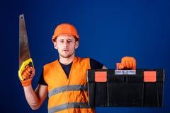 Concept de charpentier Le travailleur, le réparateur, dépanneur sur le visage sérieux porte la boîte à outils, préparent pour la  Images libres de droits