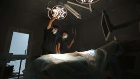 Concept de chirurgie, de médecine et de personnes - chirurgien dans le masque ajustant la lampe dans la salle d'opération à l'hôp banque de vidéos