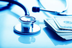 Concept de coût de soins de santé : stéthoscope et dollars Photos stock