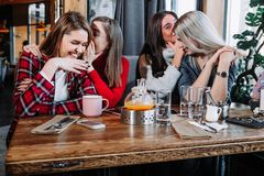 Concept de communication et d'amitié - jeunes femmes de sourire avec des tasses de café au café Photographie stock