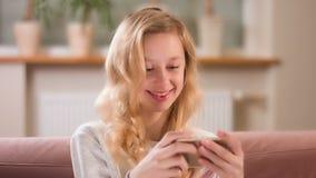Concept de consommationisme Fille blonde observant des films courts sur le media social APP clips vidéos