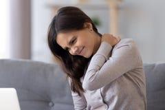 Concept de cou raide, douleur se sentante de jeune femme frottant les muscles tendus photo stock