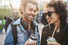 Concept de couples et d'amitié Type beau d'afro-américain marchant dans la rue avec sa soeur, café potable et Image stock