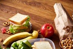 Concept de coupure de repas scolaire avec la gamelle saine et fournitures scolaires sur le bureau en bois, foyer sélectif image libre de droits