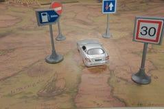 concept de course Voiture de jouet sur la carte du monde de cru avec le panneau routier image libre de droits