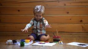 Concept de créativité et d'éducation Retrait Le garçon mignon heureux colore ses mains Faire la peinture de doigt Thérapie d'art  banque de vidéos