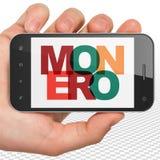 Concept de Cryptocurrency : Main tenant Smartphone avec Monero sur l'affichage Image libre de droits