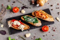 Concept de cuisine espagnole Bruschette de Tapas Different sur une baguette frite avec le basilic, tomates, fromage Plats de port image stock