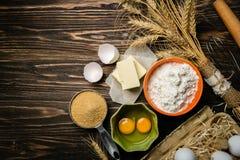 Concept de cuisson - les ingrédients de cuisson beurrent, flour, sucrent, des oeufs sur le fond en bois rustique images stock