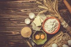 Concept de cuisson - les ingrédients de cuisson beurrent, flour, sucrent, des oeufs sur le fond en bois rustique photos stock