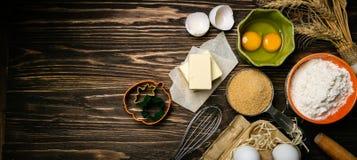 Concept de cuisson - les ingrédients de cuisson beurrent, flour, sucrent, des oeufs sur le fond en bois rustique photographie stock libre de droits
