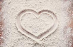 Concept de cuisson sur le fond en bois, farine arrosée avec le coeur, l'espace de copie Photos stock