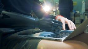 Concept de cyborg Mains artificielles et naturelles dactylographiant sur un ordinateur portable clips vidéos