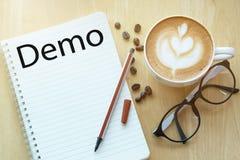 Concept de démo sur le carnet avec la tasse en verre, de crayon et de café sur la table en bois Concept d'affaires Sur la table e photographie stock libre de droits