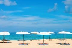 Concept de détente de plage d'Idollic avec les parasols blancs sur le sable Photographie stock