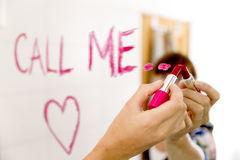 Concept de datation Les mots d'écriture de femme m'appellent sur le miroir avec le rouge à lèvres rouge Images stock