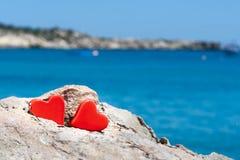Concept de deux coeurs contre la mer bleue Images stock