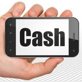 Concept de devise : Main tenant Smartphone avec l'argent liquide sur l'affichage Photo stock