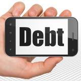 Concept de devise : Main tenant Smartphone avec la dette sur l'affichage Photographie stock libre de droits