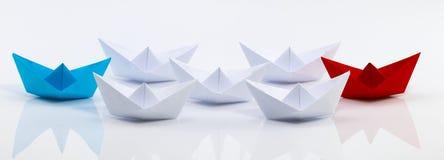 Concept de direction avec le bateau de papier rouge menant parmi le blanc Image libre de droits
