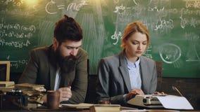 Concept de discipline L'homme avec le stylo de prise de barbe et le professeur sexy de fille imprime sur une machine à écrire, ta clips vidéos