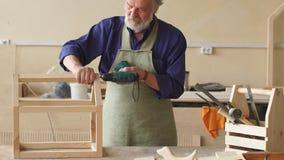 Concept de diy Le vieil homme fait un croquis de la maison d'oiseaux à partir du bois banque de vidéos