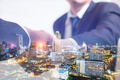 Concept de double exposition Poignée de main d'affaires d'investisseur avec le fond de nuit de ville photos libres de droits
