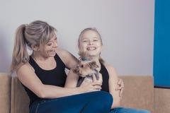 Concept de famille heureuse : maman et fille riantes jouant avec un chien de terrier de Yorkshire image libre de droits