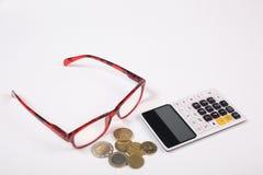 Concept de finances : calculatrice, verres de lecture et pièces de monnaie d'isolement sur le fond blanc photo stock