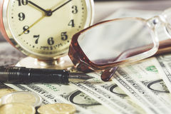 Concept de finances de style de vintage avec des verres, des billets d'un dollar, la rétro horloge, des pièces et le stylo-plume Images libres de droits