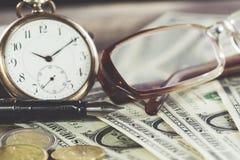 Concept de finances de style de vintage avec des verres, des billets d'un dollar, la rétro horloge, des pièces et le stylo-plume  Photo stock