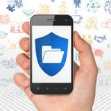 Concept de finances : Remettez tenir Smartphone avec le dossier avec le bouclier sur l'affichage Photographie stock libre de droits