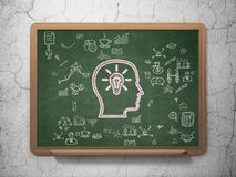 Concept de finances : Tête avec l'ampoule sur l'école Photographie stock libre de droits