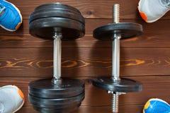Concept de forme physique Équipement de sport Les espadrilles folâtrent des chaussures et des haltères sur le fond en bois Images libres de droits