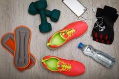 Concept de forme physique avec des chaussures, des haltères, l'eau et des espadrilles de sport Photographie stock