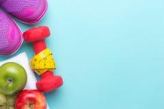 Concept de forme physique avec des fruits de mélange, des haltères, la bande de mesure et des chaussures de sport sur le fond cya Photo stock