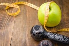 Concept de forme physique avec des haltères, pomme, centimètre Photographie stock libre de droits