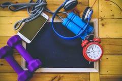 Concept de forme physique avec l'écouteur, les haltères d'horloge et le téléphone Image stock