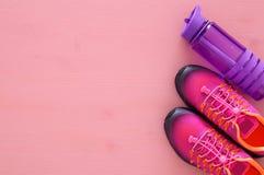 concept de forme physique avec la bouteille de chaussures roses de sport de l'eau et de femme au-dessus de fond coloré Photos libres de droits