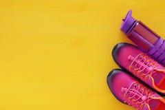 concept de forme physique avec la bouteille de chaussures roses de sport de l'eau et de femme au-dessus de fond coloré Photos stock