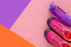 concept de forme physique avec la bouteille de chaussures roses de sport de l'eau et de femme au-dessus de fond coloré Image libre de droits