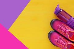 concept de forme physique avec la bouteille de chaussures roses de sport de l'eau et de femme au-dessus de fond coloré Photographie stock libre de droits
