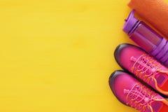 concept de forme physique avec la bouteille de chaussures roses de sport de l'eau, de serviette et de femme au-dessus de fond col Images stock