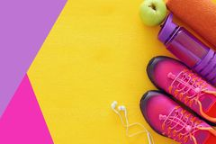 concept de forme physique avec la bouteille de chaussures roses de sport de l'eau, de serviette et de femme au-dessus de fond col Photos stock